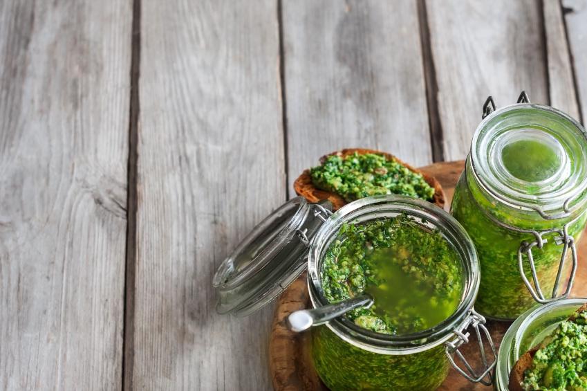 Cilantro pesto in jars on wooden background