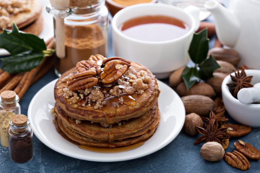 stack of spiced pancakes with brown sugar, syrup, and pecans
