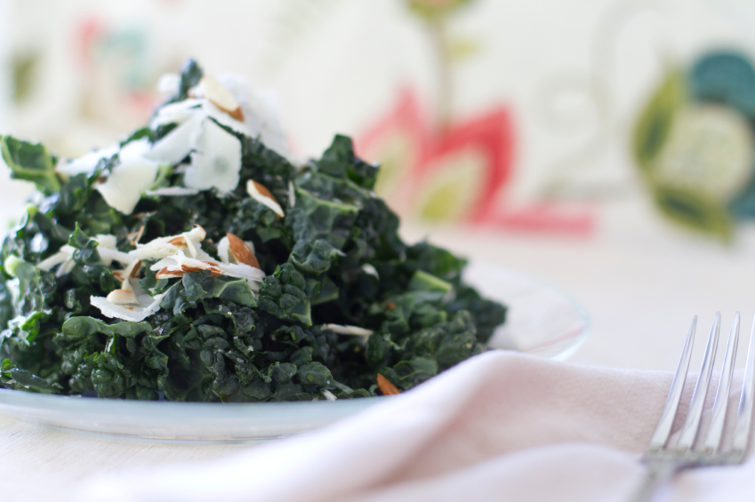 Tuscan kale salad on a white plate topped with chopped almonds and shaved Parmesan cheese