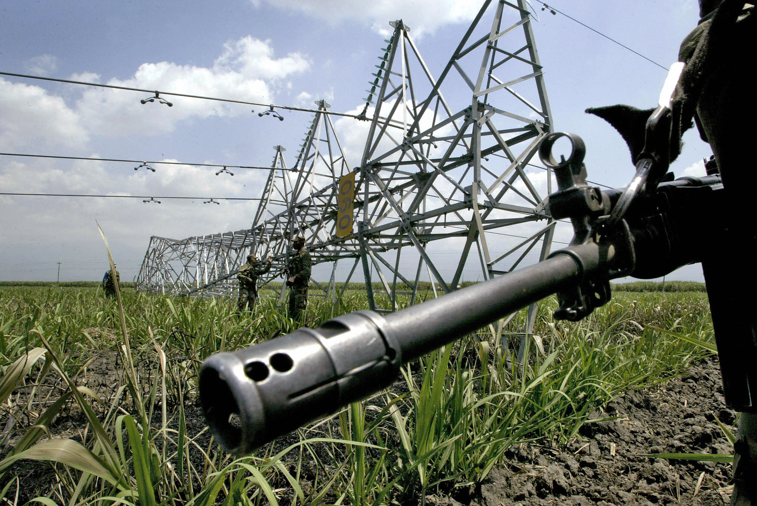 Colombian soldiers guard an electricity tower knocked down during an explosion