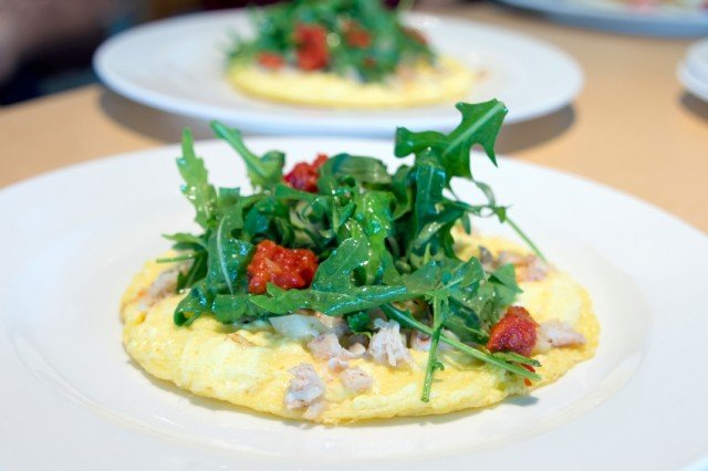 flat omelet with an arugula salad and crab topping