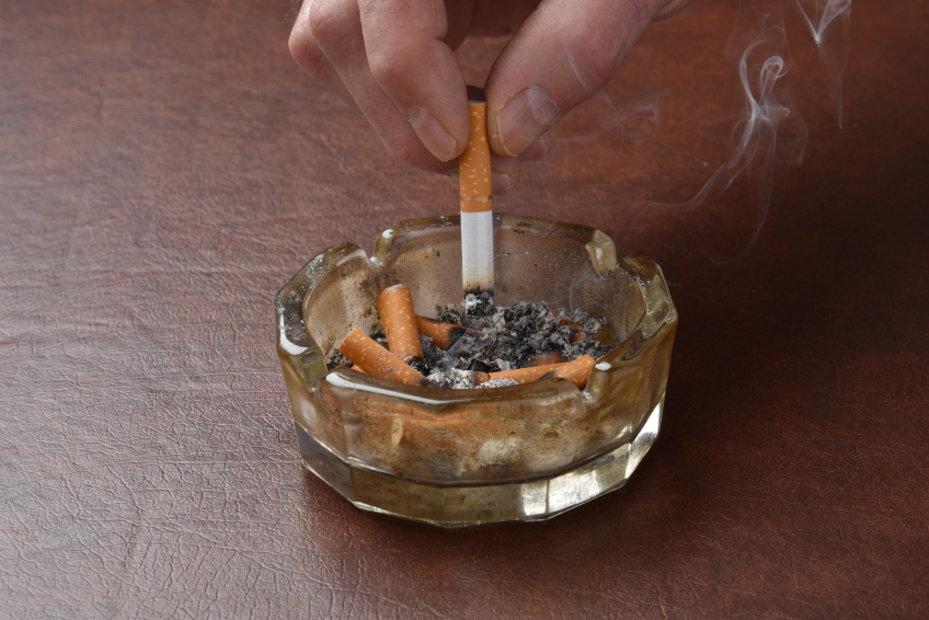 A man puts out a cigarette in an ashtray, symbolic of extinguishing the money in a bank account