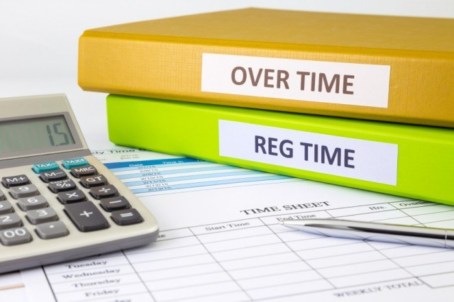 Overtime and Regular time registers with calculator on a table