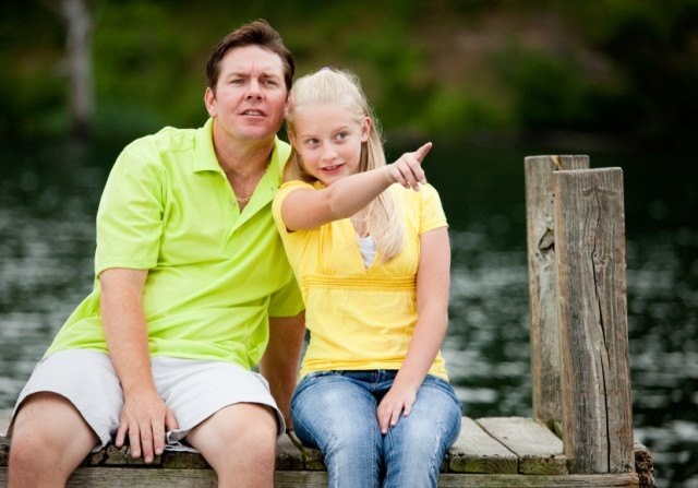 father and daughter sit on a dock overlooking a lake