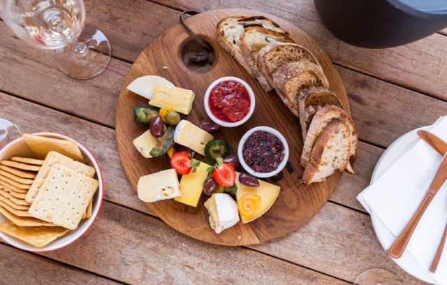 overhead image of a gourmet cheese platter served with bread and wine