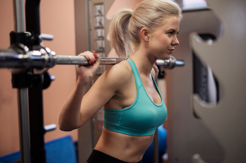 close-up of a woman's upper body as she performs barbell squats