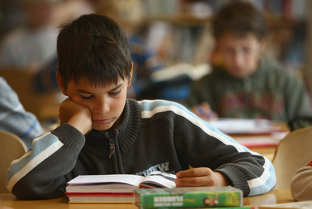 Students in an elementary classroom sit with their books open