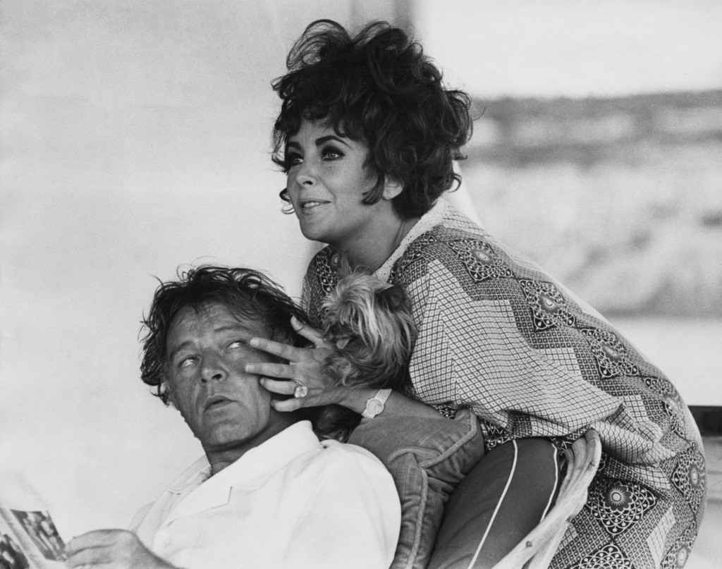 Elizabeth Taylor leans over a chair that Richard Burton is sitting in and touches his face.