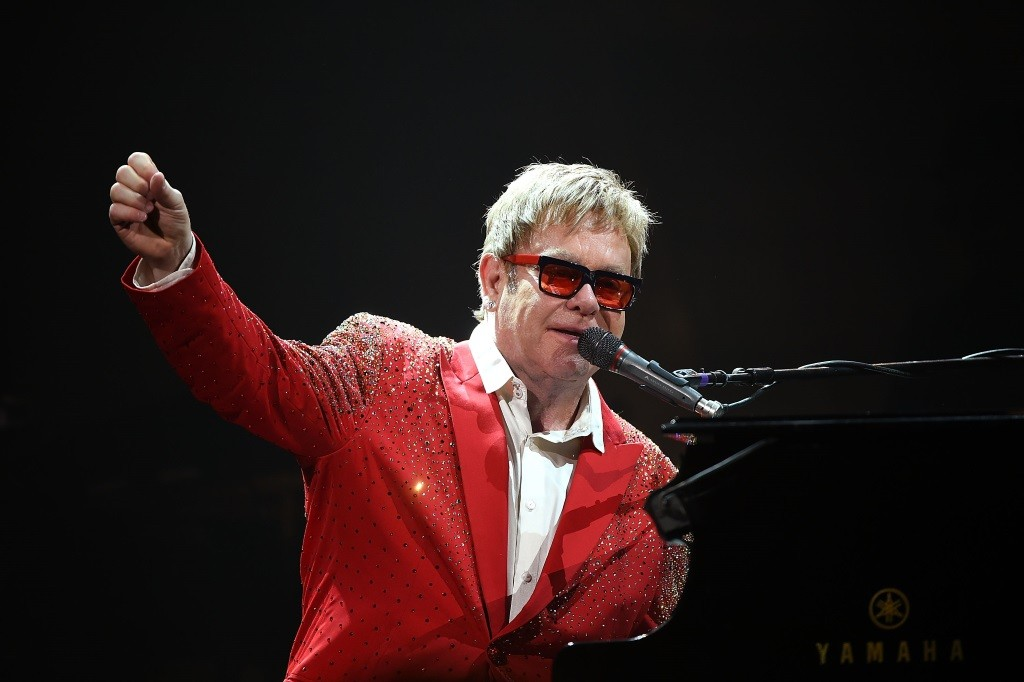 Elton John is in a red suit jacket and playing the piano on stage.