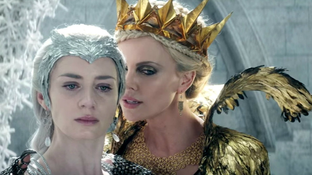 Charlize Theron as Queen Ravenna whispering in the ear of her sister, Freya the Ice Queen, played by Emily Blunt in The Huntsman Winter's War