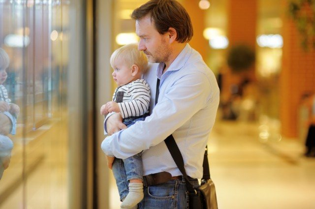 father holding an infant as he looks in a store window