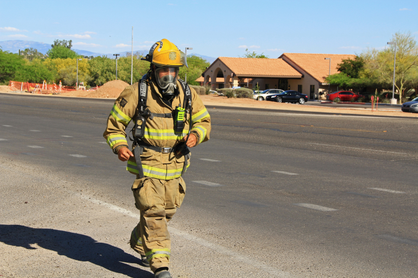 Firefighter running along the road in all of his gear