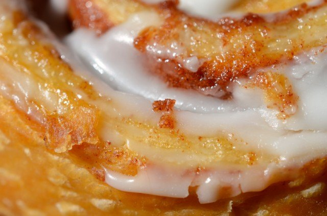 extreme close-up of an icing-covered cinnamon bun