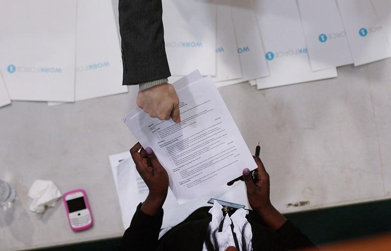 A job-seeker (top) hands his resume to a recruiter