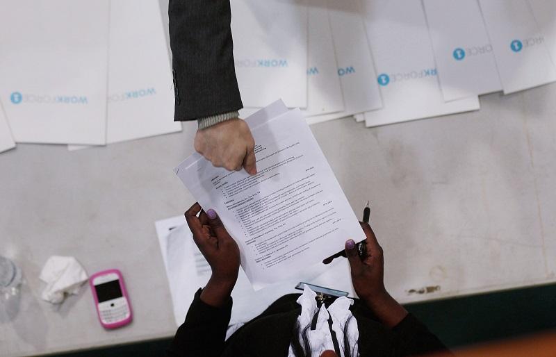 A job-seeker (top) hands his resume to a potential employer