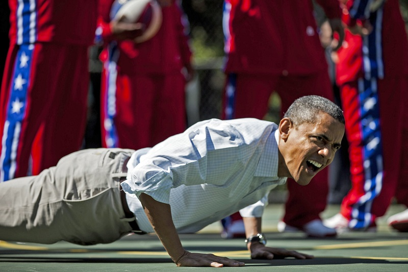 US President Barack Obama does pushups during basketball shooting drills