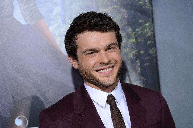 Alden Ehrenreich smiling while wearing a Burgundy suit and tie.