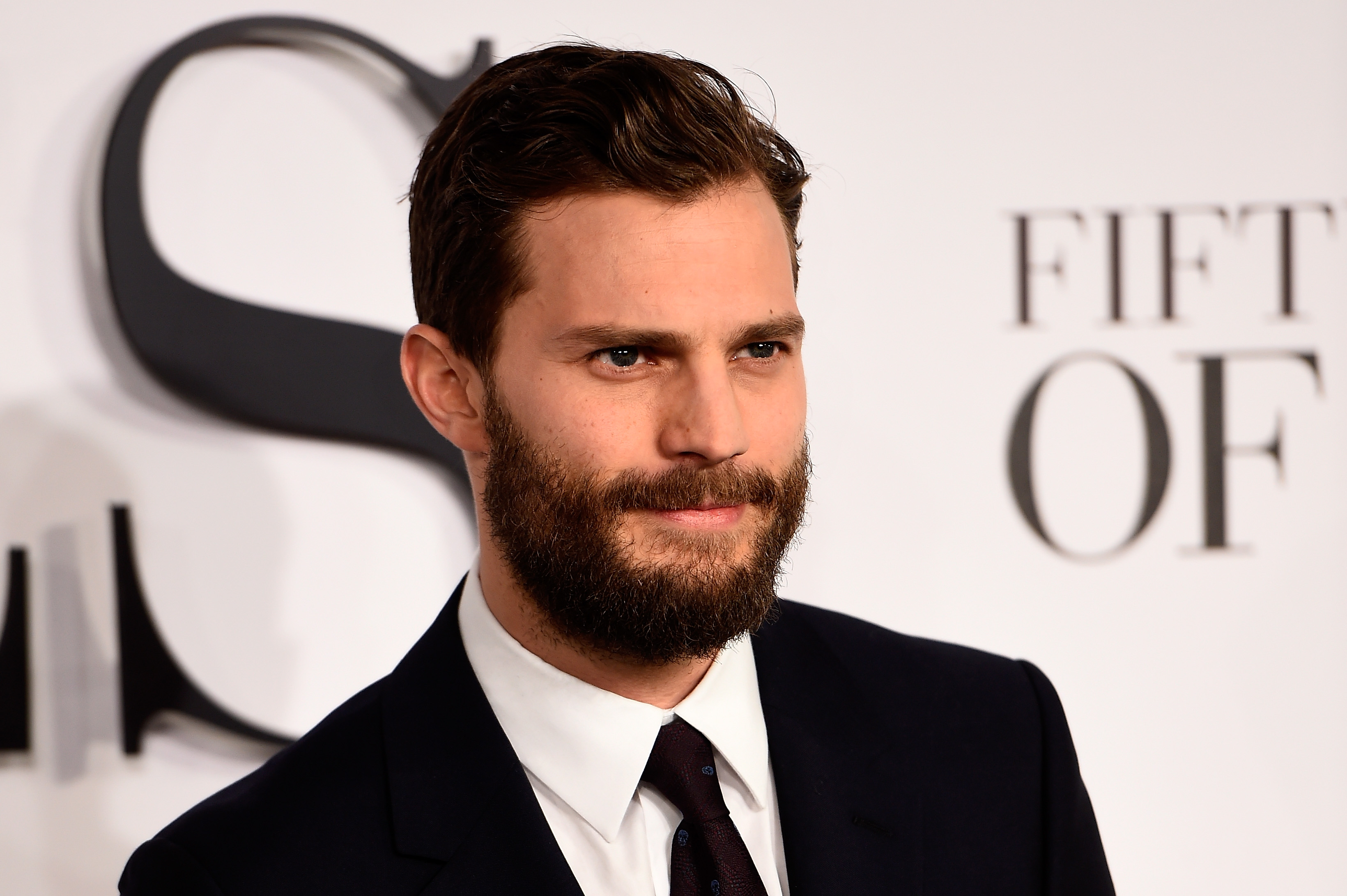 Jamie Dornan is smiling on the red carpet.