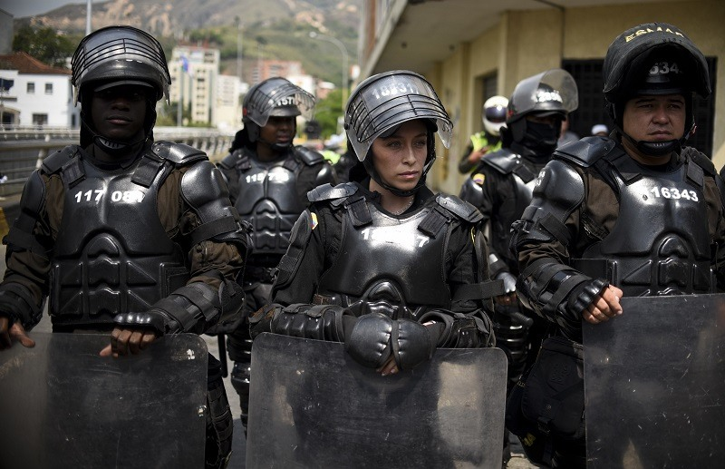 Colombian riot police guard a march in Cali, Colombia