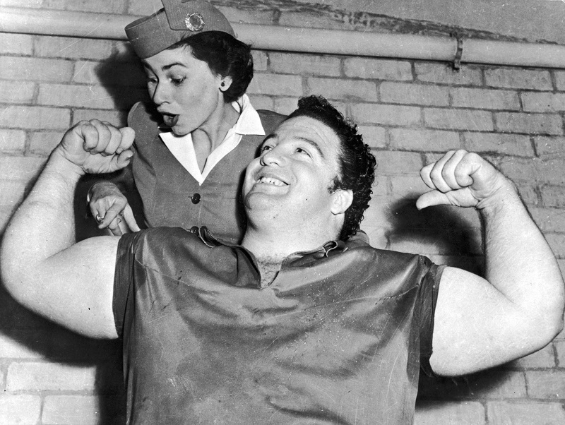 Muscle-bound member of the US Olympic weightlifting team shows off his bulging biceps to an open-mouthed stewardess