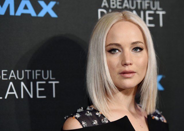 Jennifer Lawrence posing on the red carpet in a black floral dress as she stares straight ahead.