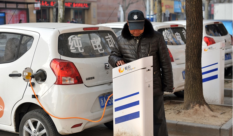 This photo taken on March 2, 2016 shows a man charging an electric vehicle at a charging point in Linan, east China's Zhejiang province. Car sales in China jumped nearly nine percent in March from a year earlier, figures from an industry group showed on April 12, a bright spot for the world's second-largest economy. The 14th Beijing International Automotive Exhibition (Auto China 2016) will take place at China International Exhibition Center New Venue (Tianzhu) and China International Exhibition Center Old Venue (Jinganzhuang) simultaneously from April 25 to May 4, 2016. / AFP / STR / China OUT (Photo credit should read STR/AFP/Getty Images)