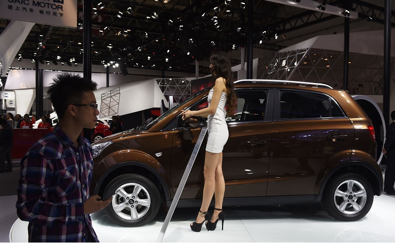 A model stands beside a Changjiang eCOOL electric car at the Beijing Auto Show in Beijing on April 26, 2016. The show is the premier annual event for carmakers to present their latest models in China, the worlds biggest auto market. China electric vehicle sales