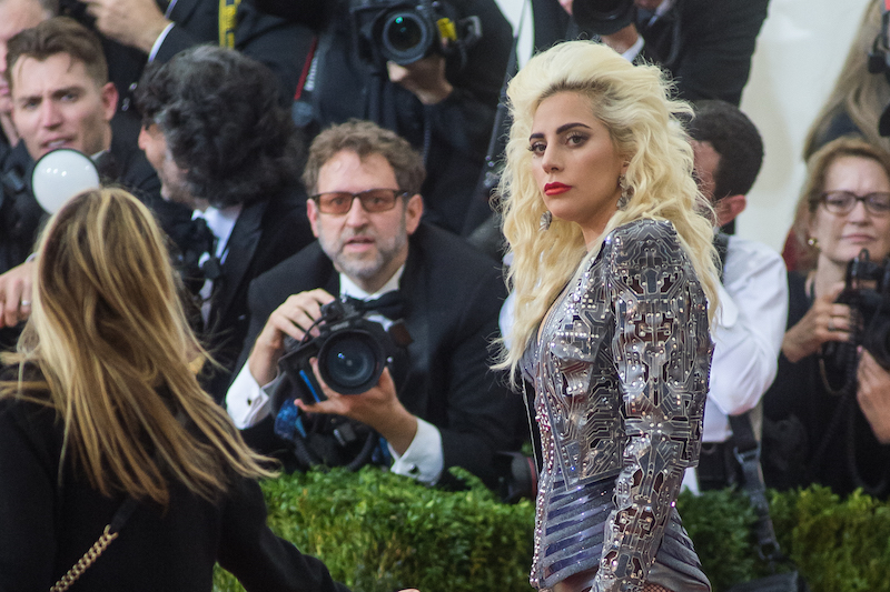 Lady Gaga is posing on the red carpet in a beaded gown with red lipstick