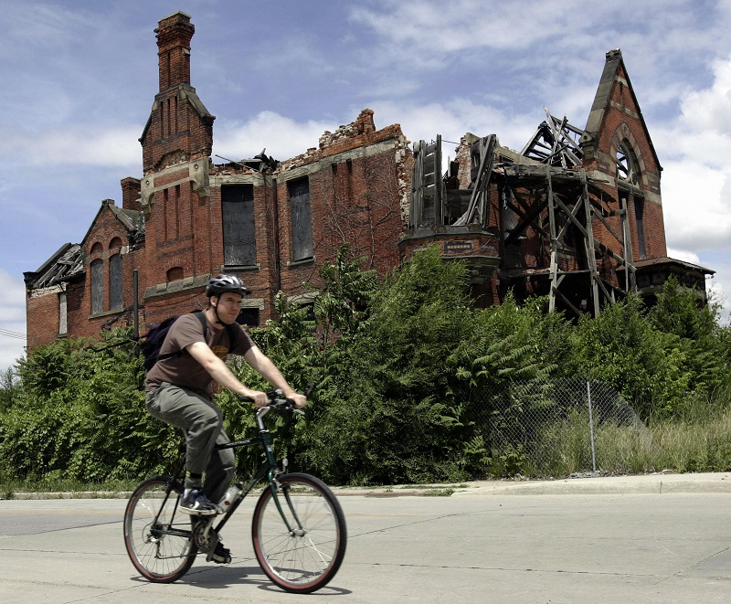 A resident passes an abandoned home in what was once a thriving middle class area in Detroit
