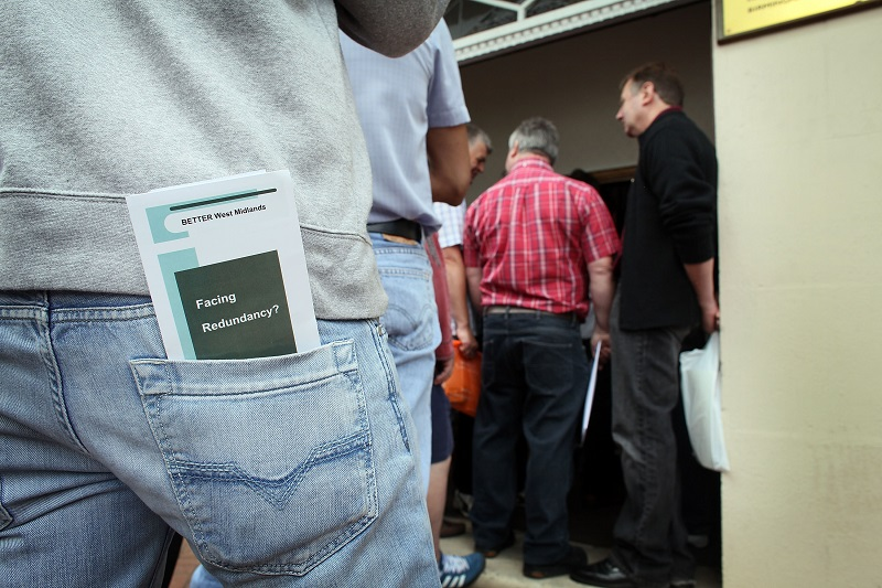 Workers wait in a queue to find out the details of their redundancy packages at an English factory