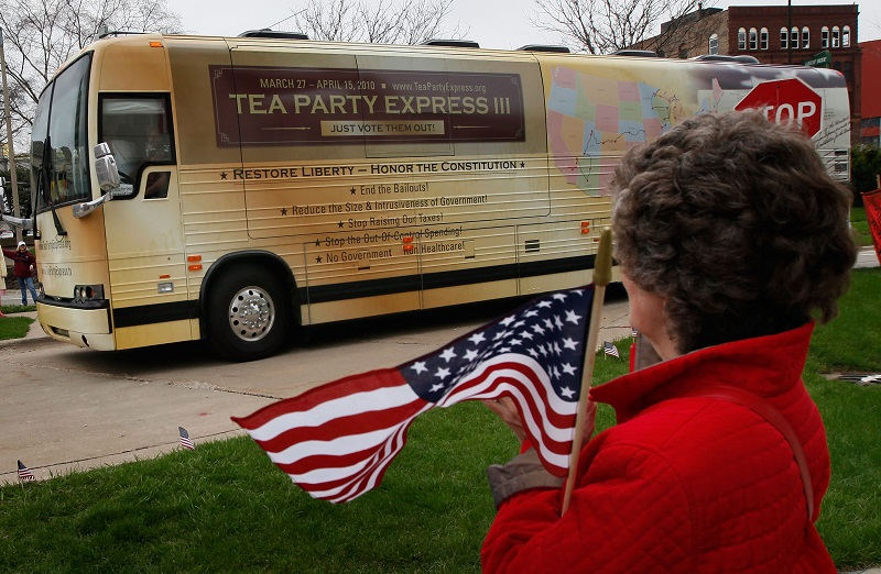A Tea Party supporter watches as buses from the Tea Party Express national tour arrive in Rockford