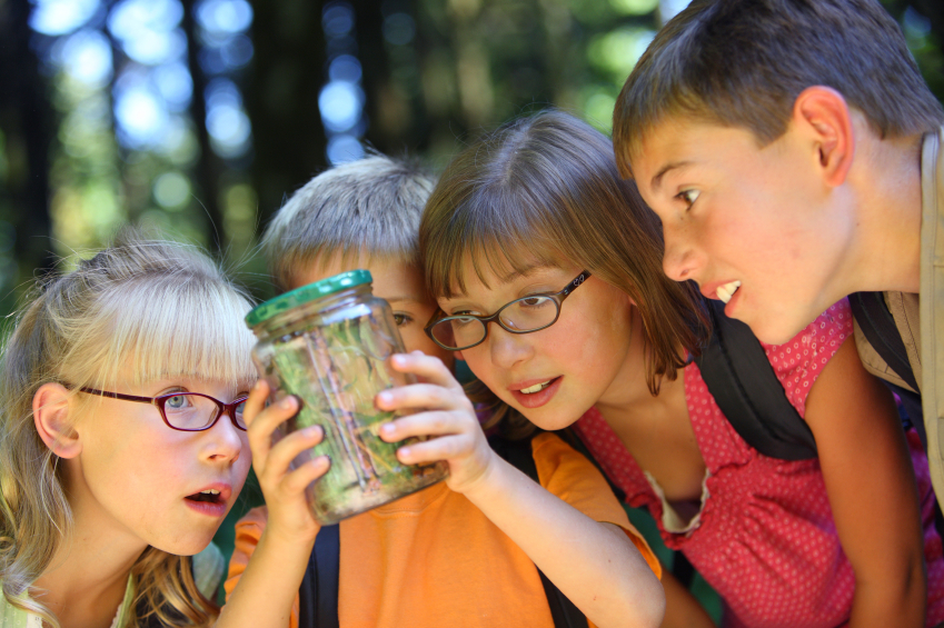 group of children outside looking at a bug they caught in a jar