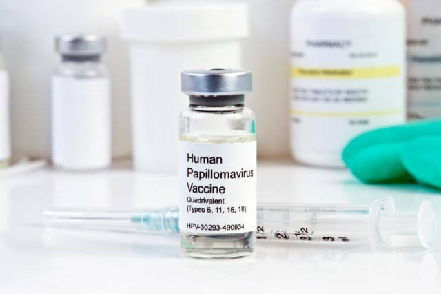 HPV vaccine in a vial next to a syringe