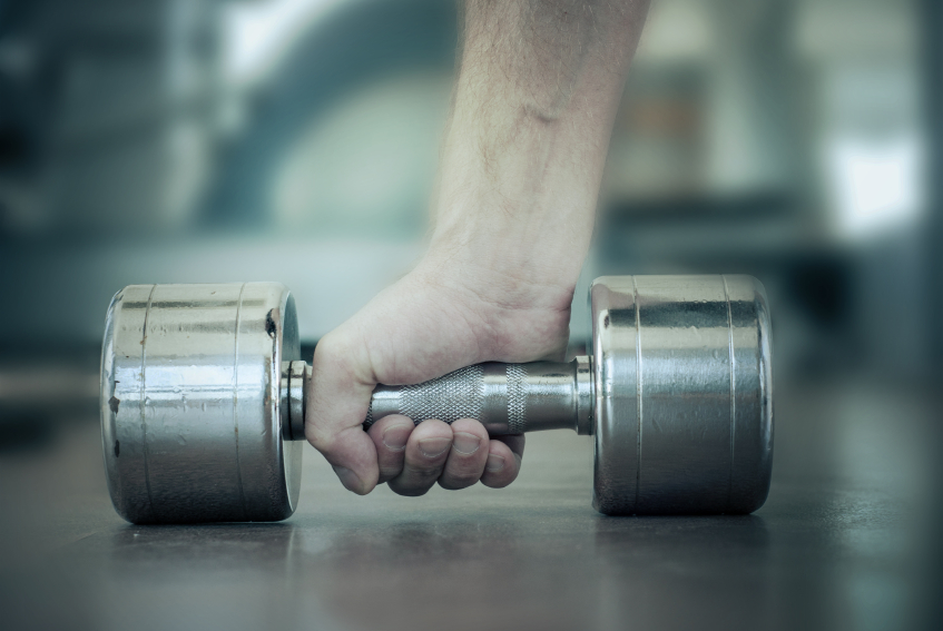 close-up of a man's hand as he chooses a dumbbell