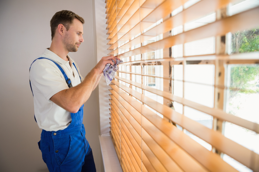 man cleaning blinds with a towel