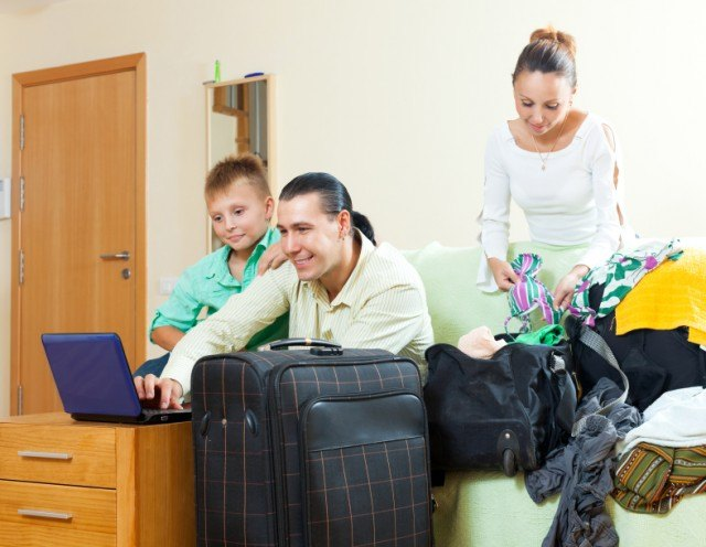 happy family of three packign while dad read something on a computer