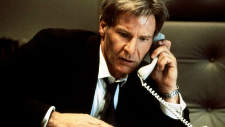 Harrison Ford wears a suit and talks on the phone as President Jim Marshall in Air Force One