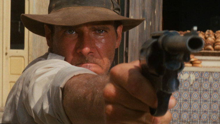 Harrison Ford aiming a gun in Raiders of the Lost Ark