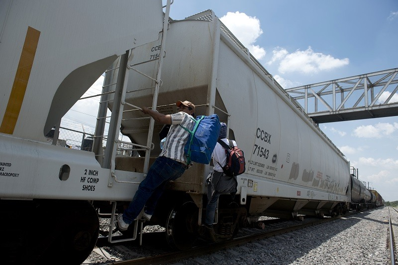 Two Honduran migrants hop a train