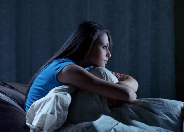 Young woman sitting up in bed at night because she can't sleep.