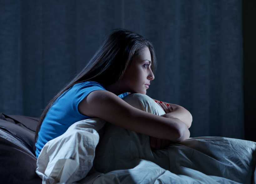 young woman sitting up in bed at night