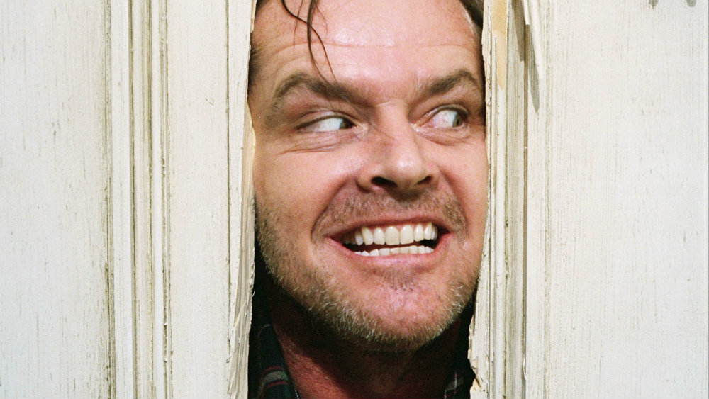 Jack sticks his face in the middle of a crack in a door in The Shining