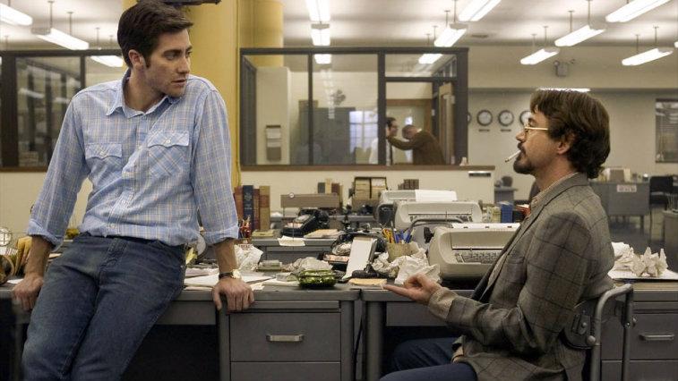Jake Gyllenhaal and Robert Downey Jr in Zodiac sitting in a newsroom