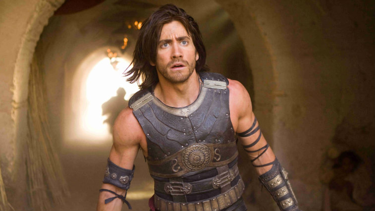 Jake Gyllenhaal looking ahead surprised in front of a tunnel wearing armor in Prince of Persia The Sands of Time