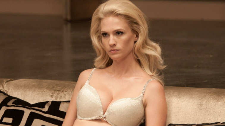 January Jones in X-Men: First Class in a bra sitting on a couch