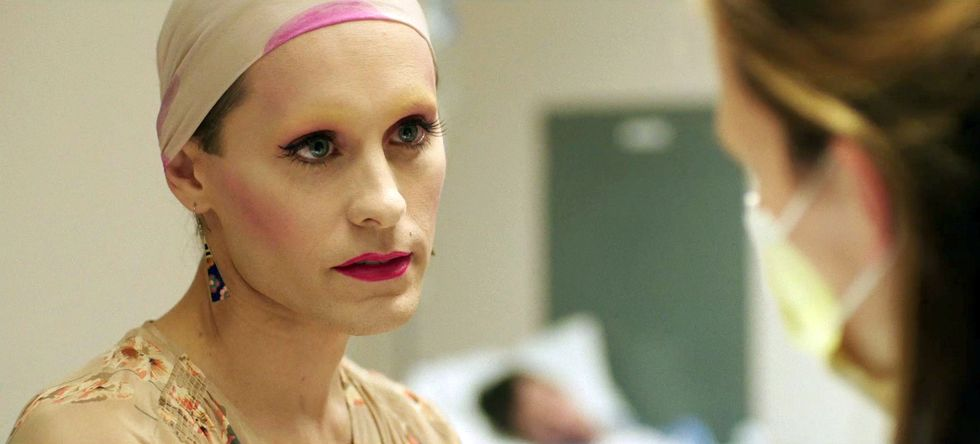 Jared Leto with full makeup, wearing a bald cap and a white dress