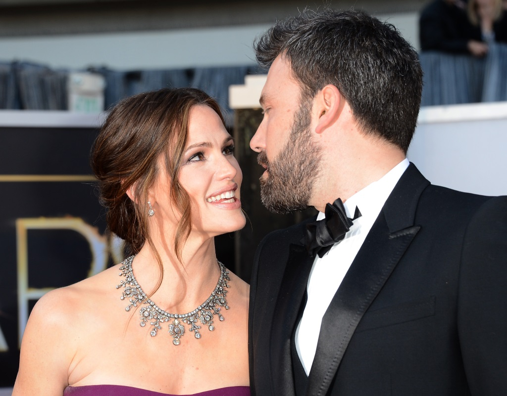Jennifer Garner and Ben Affleck smiling at each other on a red carpet.