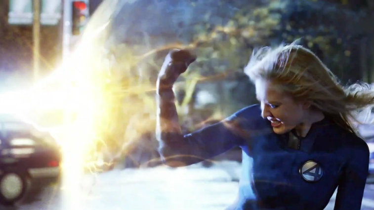 Jessica Alba in Fantastic Four, holding her right arm up to shield her from an incoming blast
