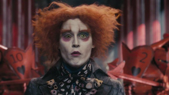 Johnny Depp wears face paint and dons red hair in 'Alice in Wonderland' seen staring straight ahead.