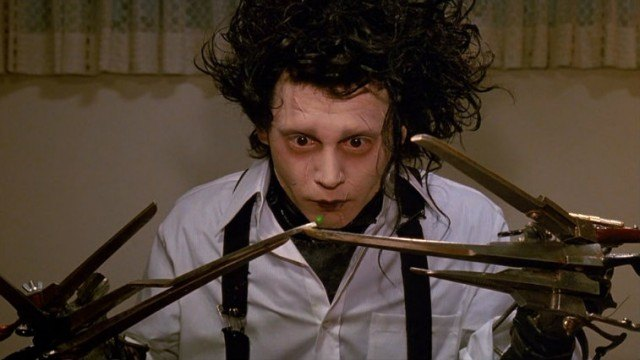 Johnny Depp holding out his scissor-hands and looking at the camera.